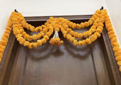 Sphinx artificial marigold fluffy flowers and rajnigandha buds triple line big door toran light orange 4